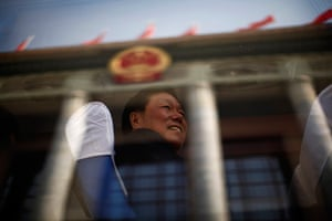 Carlos Barria China: Man travels past The Great Hall of the People on coach