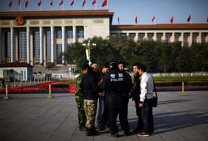 Carlos Barria China: A police officers check identifications cards in Tiananmen Square