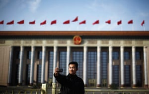 Carlos Barria China: A man takes a picture of himself in front of the Great Hall of the People