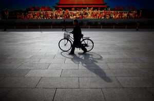 Carlos Barria China: A man walks with his bicycle in front of a screen showing propaganda