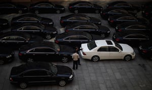 Carlos Barria China: Drivers of government cars chat at a parking lot