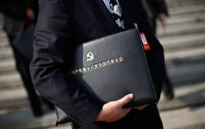 Carlos Barria China: A delegate holds a meeting bag with an emblem for the CPC