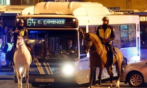 Mounted Spanish National Police officers escort a municipal bus as it leaves depots at the start of a general strike in Madrid November 14, 2012.