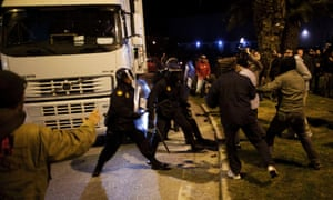 """Picketers (R) clash with riot police officers as they try to stop a truck (L) at the entrance of Malaga's main food warehouse """"MercaMalaga""""."""