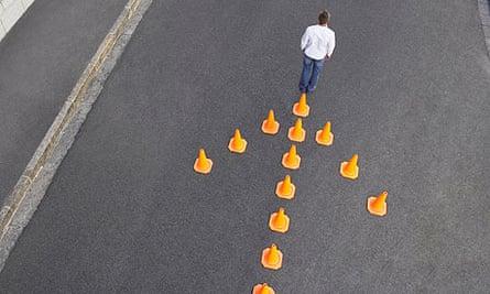 Man standing in front of traffic cones in arrow-shape