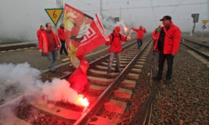 Belgian workers with flares demonstrate on rail tracks and block trains during a European strike, at the North train station in Brussels November 14, 2012.