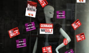 """Stickers reading """"General strike"""" are stuck on a store windowcase during a general strike  in Madrid on November 14, 2012."""