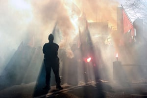 Euro protests: Lille, France: A police officer watches a man holding a flare