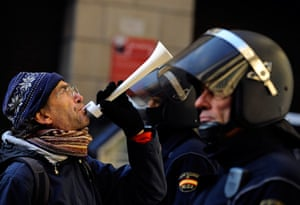 Euro protests: Pamplona, Spain: A demonstrator blows a horn in front of riot police