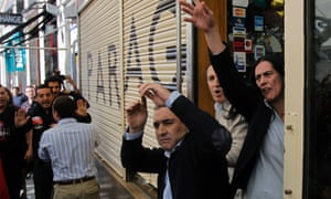 Workers from a open shop fight with the protestors who want to close it down during a general strike in Madrid, Spain, Wednesday, Nov. 14, 2012.