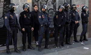 Police riots stand guard in front of a restaurant as the owner waits for the protestors to go away during a general strike in Madrid, Spain, Wednesday, Nov. 14, 2012.