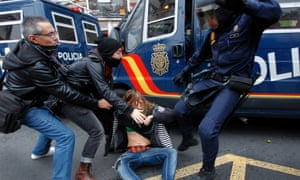 A police officer, right, kicks a woman during clashes in a general strike in Valencia, Spain, Wednesday, Nov. 14, 2012.