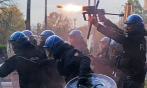A police officer fires tear gas as police face demonstrators during a protest against Italian Government austerity measures in Turin, Italy, Wednesday, Nov. 14, 2012.