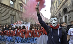In Milan, a student with V mask at the protest lights a flare.