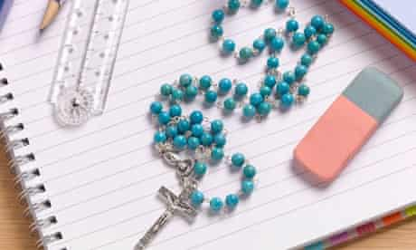 Rosary beads on top of child's school textbook