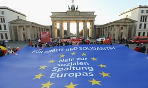 """Berlin: Protesters demonstrating in solidarity with the economically-stricken nations of southern Europe hold taut a giant flag of the European Union with slogans that read: """"For Work And Solidarity, No To The Division Of Europe"""""""