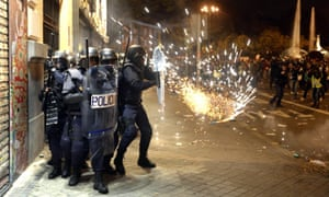 """Riot police officers protect themselves from a projectile at the end of a demonstration organized by Spain's """"indignant"""" protesters, a popular movement against a political system that they say deprives ordinary Spaniards of a voice in the crisis, near the parliament building in Madrid during a general strike on November 14, 2012."""