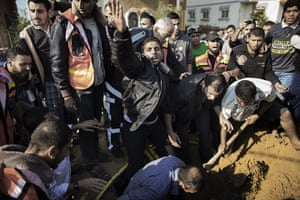 Gaza and Israeli strikes: A Palestinian man calls for help as he and others try to save a man