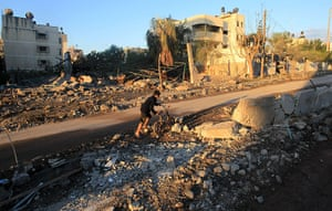 Strikes update: A Palestinian boy pushes his bycicle through the rubble