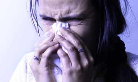 A woman with a cold blows her nose