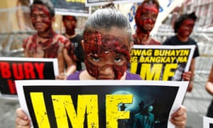 Filipino protesters dressed up as zombies hold their placards in a rally during the visit of International Monetary Fund (IMF) Managing Director Christine Lagarde