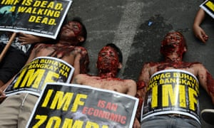 Protesters wearing Zombie masks lie on a pavement at a rally near Malacanang Palace in Manila on November 16, 2012, to coincide with a visit by International Monetary Fund (IMF) managing director Christine Lagarde.