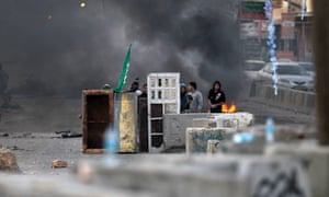 Palestinian youth take cover behind a makeshift barrier during clashes with Israeli soldiers at the Qalandia checkpoint, in the occupied West Bank, on November 16, 2012 during a protest against the war on Gaza.