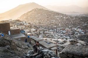 20 Photos: An Afghan boy climbs a rock fence in Kabul, Afghanistan