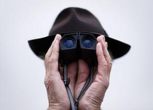 20 Photos: A gentleman watches the action through binoculars at Cheltenham racecourse