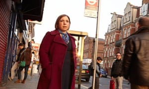 Sarah Teather looking into the distance by bus stop in busy London street