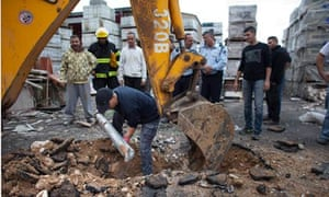 An Israeli policeman pulls a rocket launched from Gaza out of the ground in Netivot