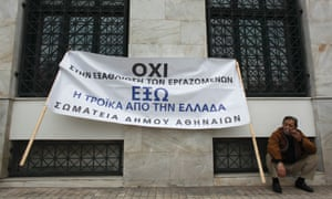 "A protester smokes as he takes part in a rally organised by municipality workers against state sector layoffs demanded by the country's international lenders, outside the city hall in Athens November 19, 2012. The banner reads, ""No to the impoverishment of workers, troika get out of Greece."""