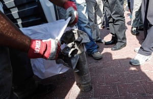 Gaza conflict: Israeli police collect the remains of a palestinian rocket