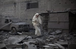 Gaza conflict: A women walks through the remains of a house