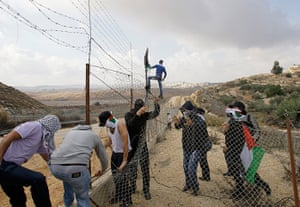 Gaza conflict: Palestinian protesters cut a section of the West Bank separation barrier