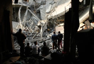 Gaza conflict: Palestinians look at a destroyed house after an Israeli air strike in Gaza