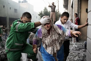 Gaza conflict: A woman is evacuated by a paramedic