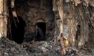 Woman searches through debris of destroyed shops in Karachi