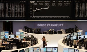 Traders are pictured at their desks in front of the DAX board at the Frankfurt stock exchange November 19, 2012.