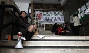 Agriculture ministry workers are seen at the entrance to the ministry headquarters in Athens, which was occupied by protesting employees on Monday, Nov. 19, 2012.