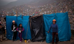 At your convenience: the owners of makeshift public toilets wait for customers. They charge about 15 cents per person for use of the facilities, at the Virgen de Lourdes cemetery where relatives converged to honour dead friends and family, on the Day of the Dead holiday, in Lima, Peru