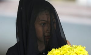 Ara Marcellana, a daughter of missing activist Eden Marcellana, holds a bouquet of flowers prior to a performance to mark the observance of All Souls' Day outside a Roman Catholic church in Paranaque, south of Manila, in the Philippines. The families of missing activists have banded together to seek justice for their relatives have been missing for several years. Photograph: Bullit Marquez/AP