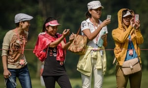 Chinese golf fans take pictures with their smartphones during the second round of the WGC-HSBC Champions golf tournament held on the Olazabal course at Mission Hill Golf Club in Dongguan.