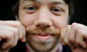 A young man shows off his Movember moustache