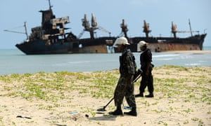 Sri Lankan soldiers use metal detectors to search for landmines and buried weapons, while the Jordanian ship Farah-3, which ran aground after being captured by Tamil Tiger rebels in December 2006, is seen in the background. The troops uncovered a cache of weapons exposed by recent storm surges and heavy rains near the north-eastern town of Vellamullivaikkal. Photograph: Ishara S.Kodikara/AFP/Getty Images