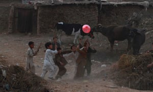 Boys play with a balloon in a slum on the outskirts of Islamabad, Pakistan.