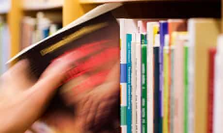 Hand taking out a book from a bookshelf in a library.
