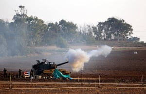 Israel Gaza : Israeli soldiers stand near a mobile artillery unit as it fires a shell