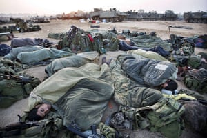 Israel Gaza : Israeli soldiers sleep near armoured personnel carriers