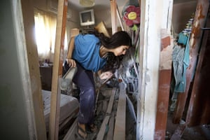 Israel Gaza : A woman retrieves one of her shoes from her damaged home